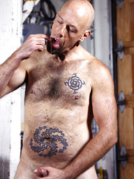 Tattooed hairy bear Budd Cort rubs his fat dick and licks his precum