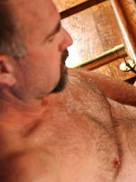 Clint Taylor has a hairy chest and a thick mature dick that this bear strokes at the bar