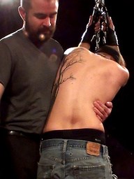 Sir has the boy right where he wants him, arms chained to the ceiling and awaiting punishment.