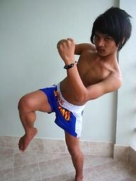 Cute gay Thai kickboxer posing and stripping