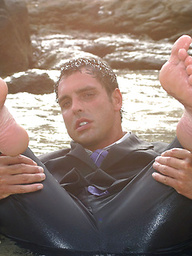 Marcello wearing a soaking wet business suit wanking on the rocks